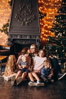 Gran familia en nochebuena con regalos por árbol de navidad