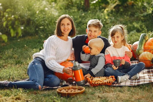 Gran familia sentada en un jardín cerca de muchas calabazas