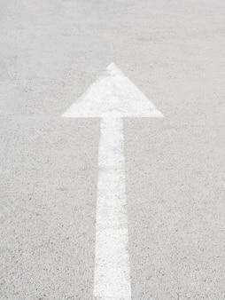 Gran flecha blanca sobre asfalto