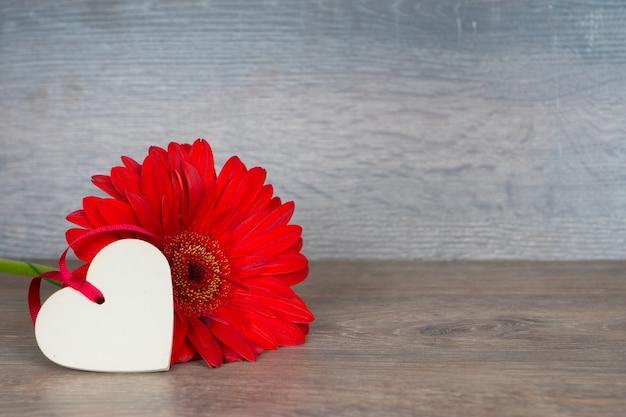 Gran flor roja con forma de corazón en la mesa de madera rústica