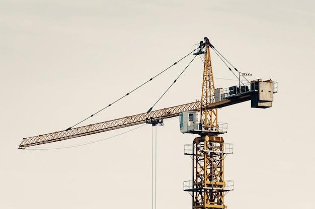 Gran grúa torre contra el cielo en tonos desvaídos. primer plano de equipos de construcción con copyspace. construir de ciudad.