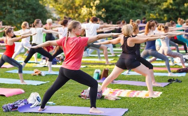 Gran grupo de adultos que asisten a una clase de yoga afuera en el parque