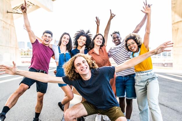 Gran grupo de amigos felices se encuentra en las calles de la ciudad con los brazos levantados junto a la gente
