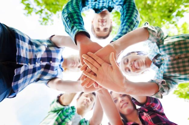 Gran grupo de amigos sonrientes permanecer juntos y mirando a cámara aislada sobre fondo azul.