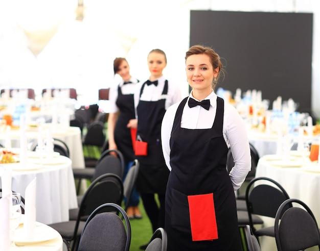 Gran grupo de camareros y camareras de pie en fila