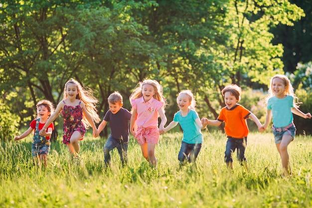 Gran grupo de niños, amigos, niños y niñas corriendo en el parque en un día soleado de verano con ropa informal.