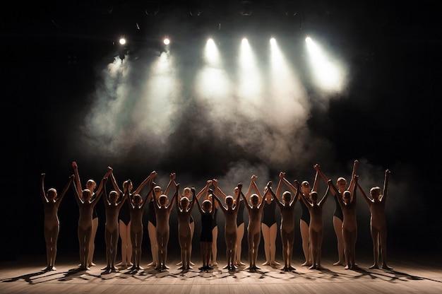 Un gran grupo de niños tiene una reverencia al final de la actuación.