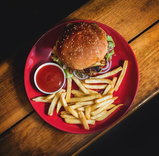 Gran hamburguesa con queso y patatas fritas en un plato.