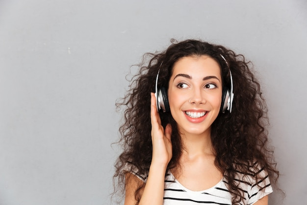 Gran imagen de mujer caucásica rizada en camiseta a rayas en auriculares disfrutando de la música a través de un dispositivo moderno mientras descansa