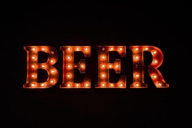 Gran inscripción luminosa cerveza de bombillas, en la oscuridad