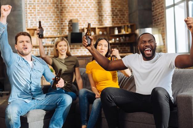 Gran juego. cuatro lindos amigos emocionados enérgicos bebiendo mientras están sentados en el sofá y celebrando la victoria