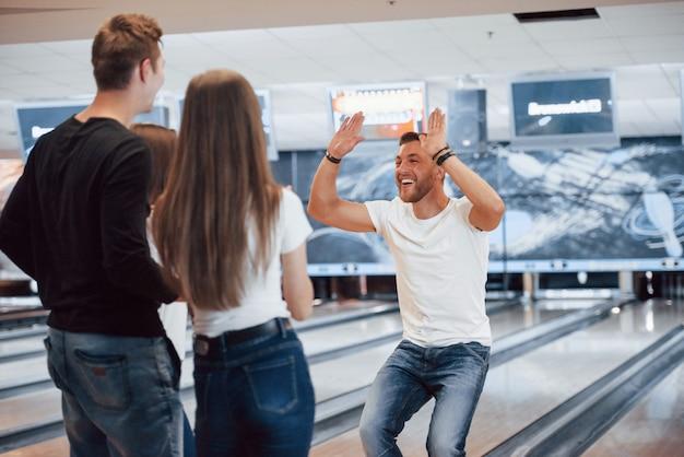 Gran juego. jóvenes amigos alegres se divierten en el club de bolos en sus fines de semana