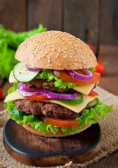 Gran jugosa hamburguesa con verduras y carne en una mesa de madera en estilo rústico