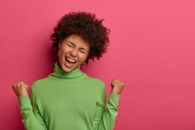 Gran logro y concepto de éxito. feliz mujer afroamericana aprieta los puños, hace un gesto de victoria, grita sí, inclina la cabeza, viste un jersey de cuello alto verde