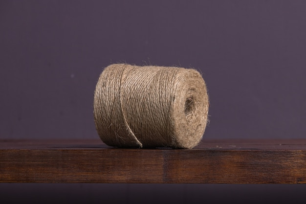 Una gran madeja de hilo marrón se encuentra en un estante de madera