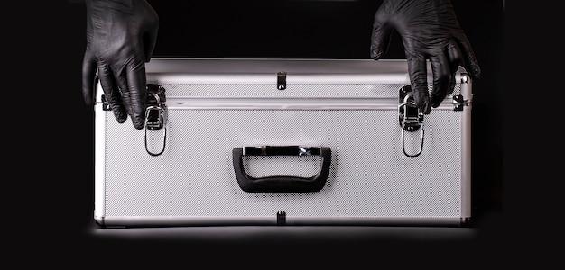 La gran maleta de aluminio y las manos guantes de seguridad negros.