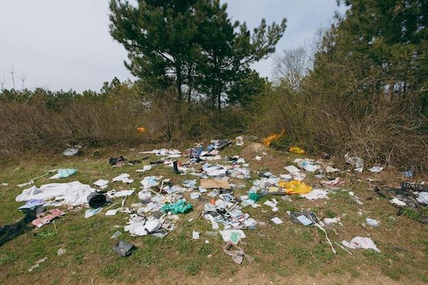 Gran montón de basura entre arbustos y árboles en un parque o bosque lleno de basura