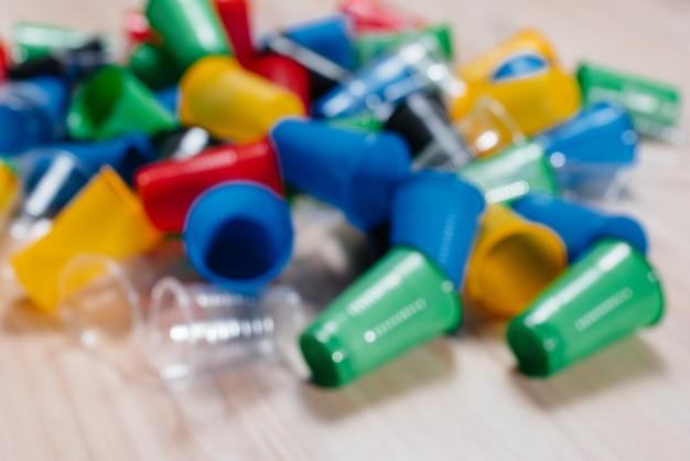 Un gran montón de vasos de plástico multicolores esparcidos por el suelo con espacio libre, desenfocado. contaminación del medio ambiente por desechos humanos.
