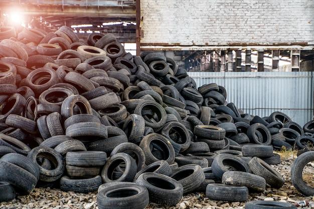 Gran montón de viejos neumáticos negros de diferentes vehículos que yacen en la planta abandonada.