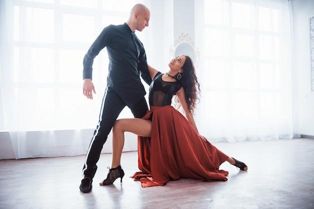 Gran movimiento joven mujer bonita en ropa roja y negra bailando con calvo en la sala blanca