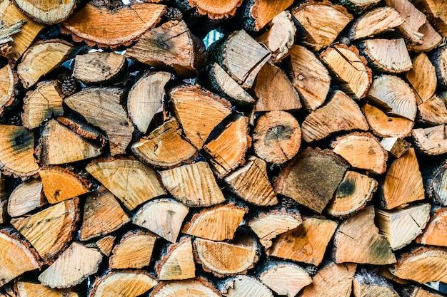 Gran muro de troncos de madera apilados que muestran decoloración natural