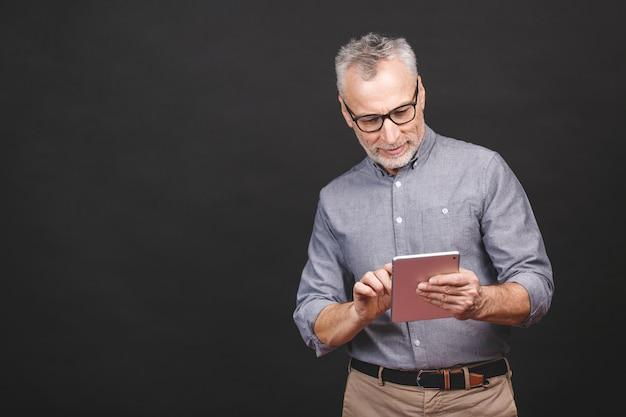 ¡una gran noticia! apuesto hombre de negocios maduro en ropa casual elegante y anteojos está usando una tableta digital y sonriendo