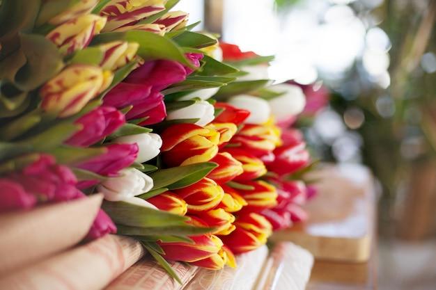 Un gran número de tulipanes yacen sobre la mesa para prepararse para la venta en el mercado o en la tienda. vista lateral