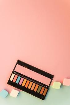 Gran paleta de maquillaje con esponja colorida sobre doble fondo.