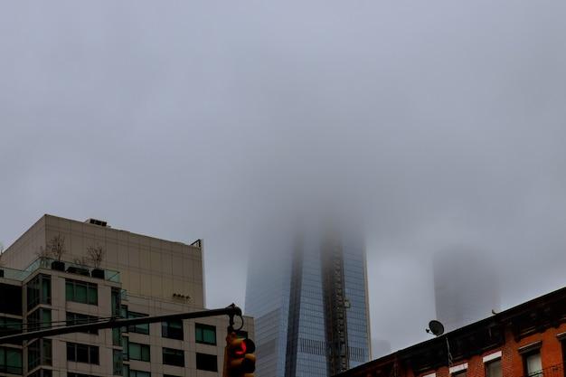 Gran perspectiva de un edificio filmado desde abajo en un día nublado con niebla.