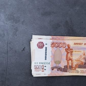 Gran pila de billetes de dinero ruso de cinco mil rublos sobre un cemento gris.