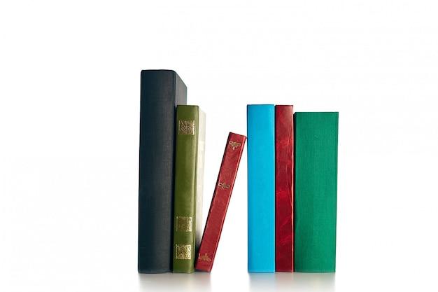 Gran pila de viejos libros antiguos aislados en la pared blanca