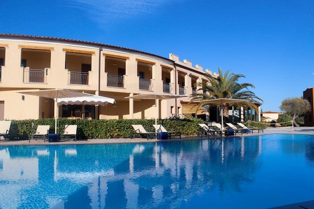 Gran piscina cerca del hotel en un resort en san teodoro, cerdeña