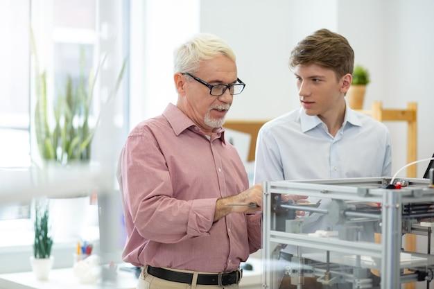 Gran profesor. agradable ingeniero senior que muestra a su becario cómo tomar medidas con la pinza mientras imprimen modelos 3d juntos