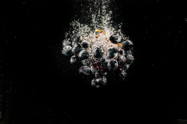 Gran racimo de uva negra salpica el agua que cae en el acuario