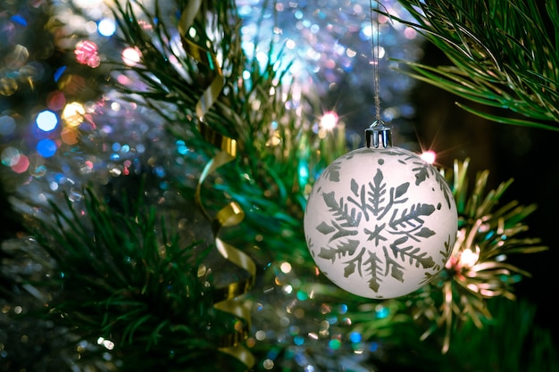Gran recipiente de vidrio con un patrón de copos de nieve. juguetes de navidad en el árbol de navidad.