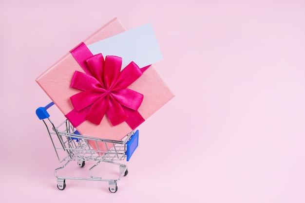 Gran regalo en el carrito de la compra con una nota simulada sobre un fondo rosa