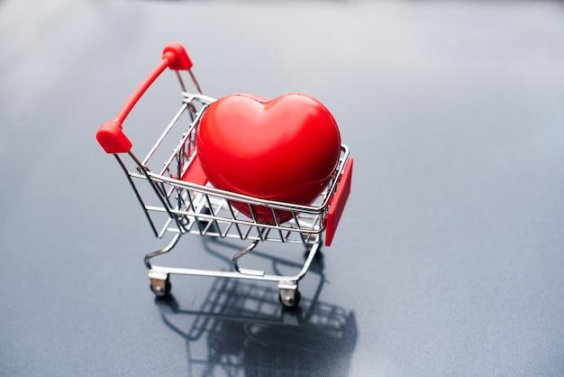 Gran regalo de corazón en carrito de compras.