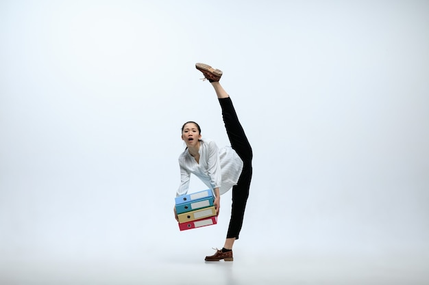 Gran responsabilidad. mujer sufriente que trabaja en la oficina, saltando y bailando en ropa casual o traje aislado sobre fondo blanco de estudio. negocio, puesta en marcha, concepto de espacio abierto de trabajo.
