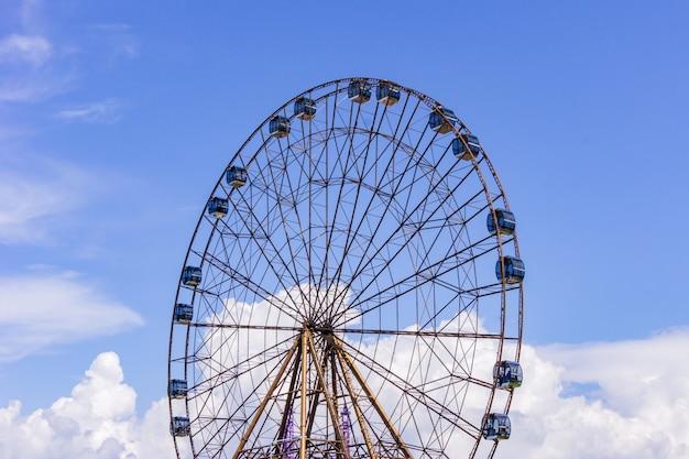 Gran rueda de la fortuna atraktsion en el fondo de un hermoso cielo azul con nubes