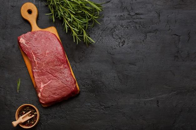 Gran sabrosa carne cruda en tabla de cortar con romero. vista superior, copia espacio.