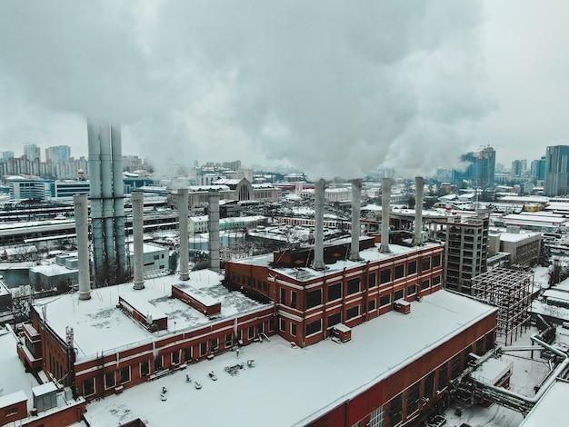 Gran sala de calderas central con tuberías gigantes de las cuales hay humo peligroso en invierno durante las heladas en una gran ciudad