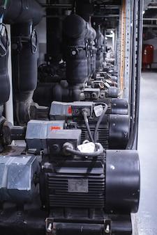 Gran sala de tratamiento de aguas industriales y caldera. tubos negros, bombas y válvulas.