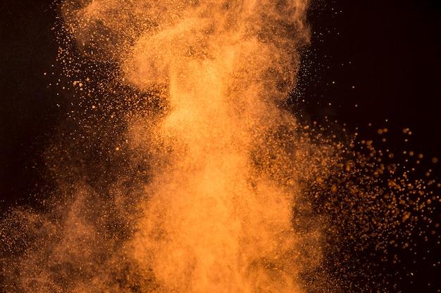 Gran salpicadura de polvo de maquillaje naranja sobre fondo oscuro
