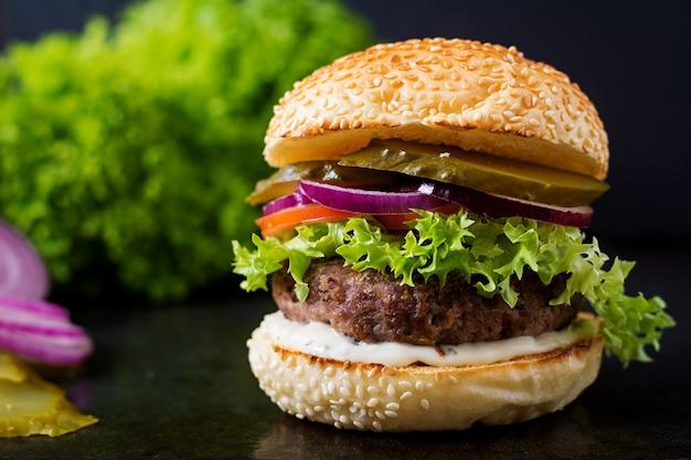 Gran sándwich - hamburguesa con carne de vacuno, encurtidos, tomate y salsa tártara sobre fondo negro.