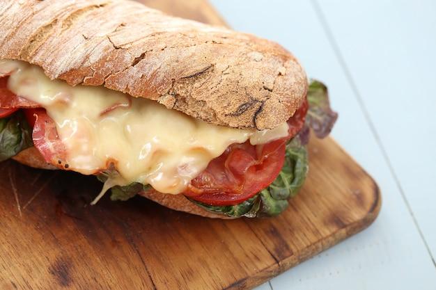 Gran sandwich vegano con verduras en la mesa de tablero de madera
