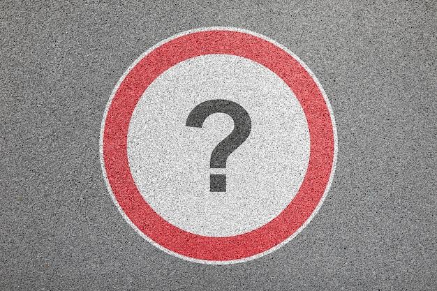 Gran señal de tráfico redonda pintada en primer plano de superficie de asfalto