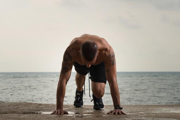 Gran tipo musculoso haciendo flexiones en el suelo