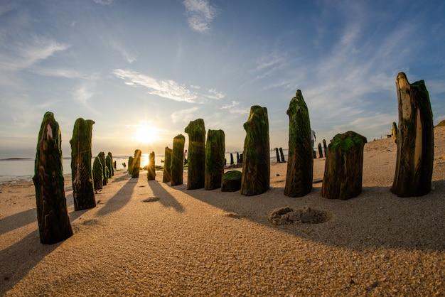 Gran tiro de ojo de pez de piedras verticales cubiertas de musgo verde en una playa de arena en un día soleado