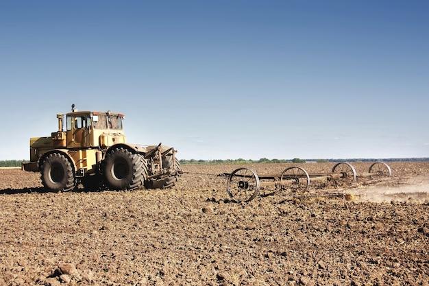Gran tractor amarillo equipado con grada trabajando en el campo.