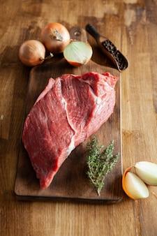 Un gran trozo de rojo se unió en una tabla de cortar vintage junto a cebollas blancas. romero verde. frijoles de pimienta.